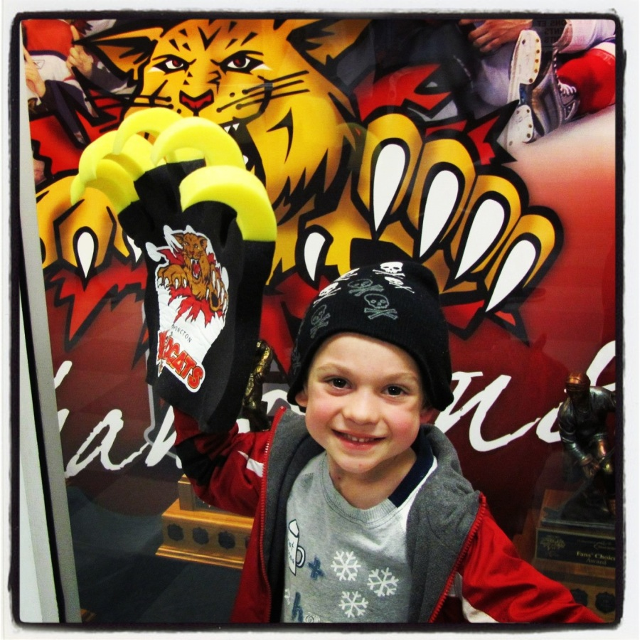 """10-19-12 -- I was a bit excited to be able to take Ankle Biter to his first hockey game. He was quite excited to watch the Moncton Wildcats play (he also couldn't contain his excitement at getting a """"claw"""" of his very own)."""