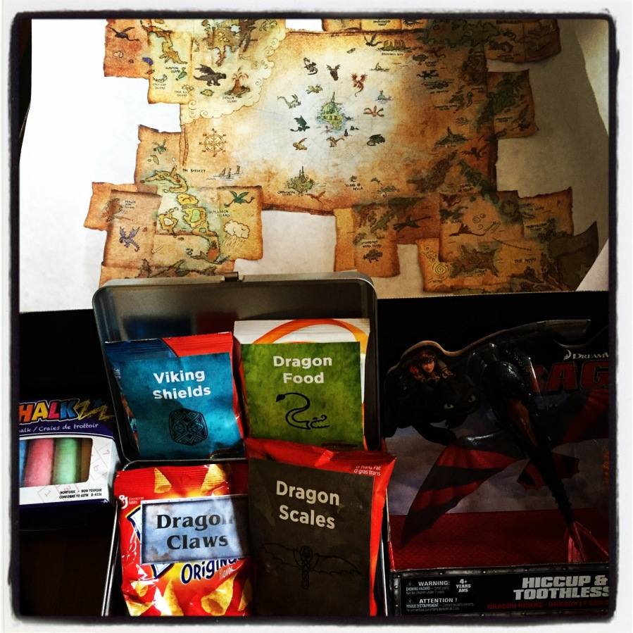 This is most of what was inside the package. A copy of the map that Hiccup made, some sidewalk chalk, a toy featuring Hiccup and Toothless, and some snacks that were re-labeled to fit the package (Doritos were